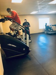 photo of people on exercise equipment with coach in background