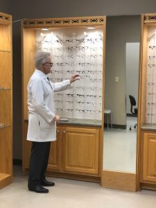 Optometrist selecting a pair of glasses from shelf